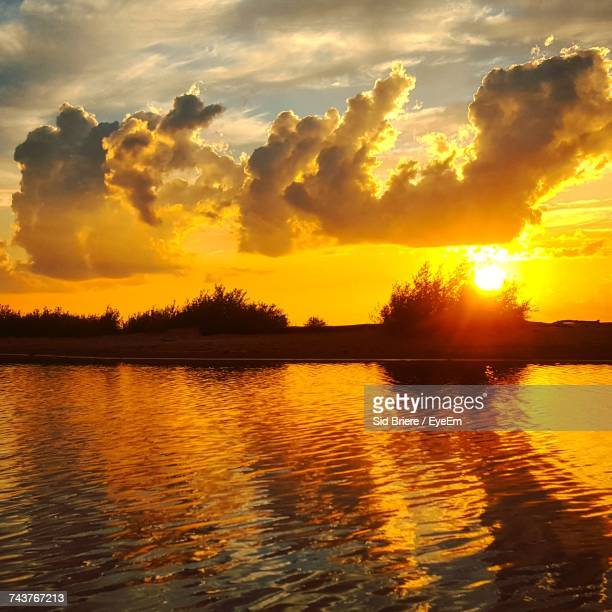Scenic View Of Lake Against Dramatic Sky During Sunset
