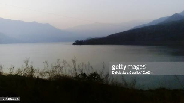Scenic View Of Lake And Mountains Against Sky At Sunset