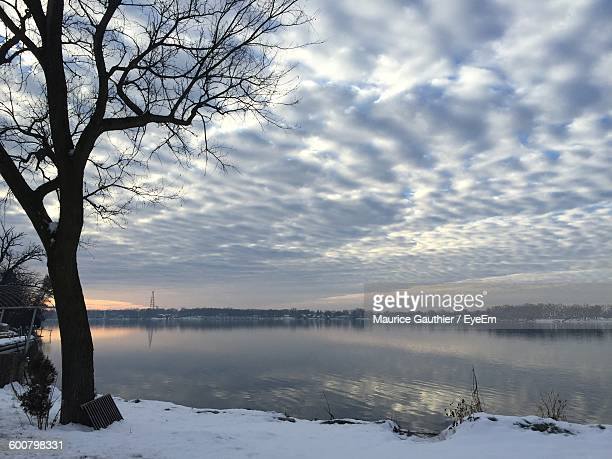 Scenic View Of Lake And Snow Covered Field Against Cloudy Sky During Sunset