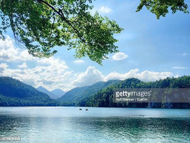 Scenic View Of Lake By Mountains Against Cloudy Sky