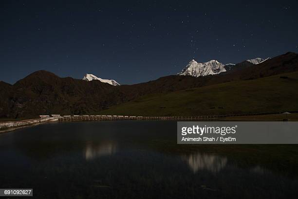 Scenic View Of Lake By Mountains Against Sky At Dusk