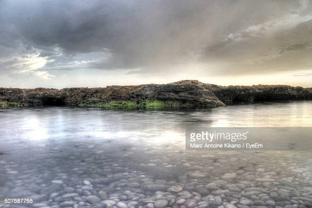 Scenic View Of Lake By Rock Against Cloudy Sky