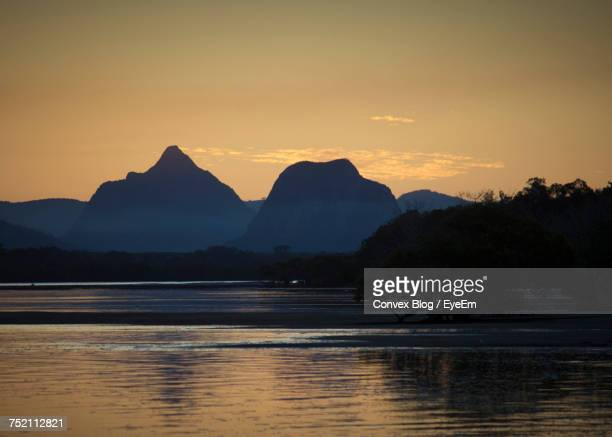 Scenic View Of Lake By Silhouette Mountains Against Sky During Sunset