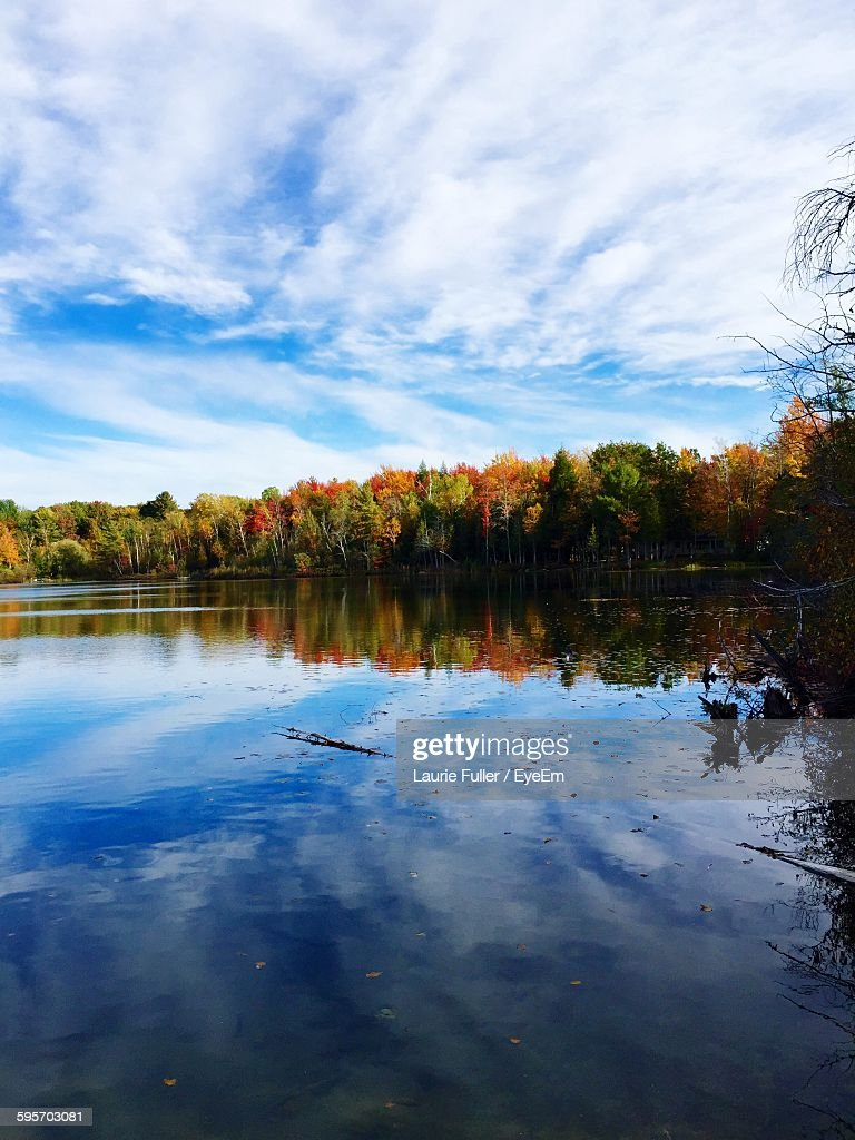 Scenic View Of Lake By Trees Against Cloudy Sky At Autumn