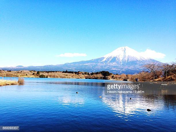 Scenic View Of Lake In Front Of Snowcapped Mountains Against Blue Sky