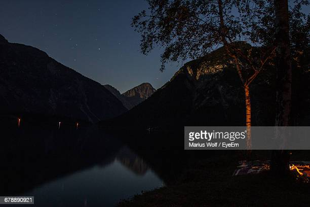 Scenic View Of Lake With Mountains Reflection At Night