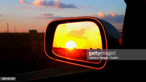 Scenic View Of Landscape Against Sky Seen Through Side-View Mirror Of Car
