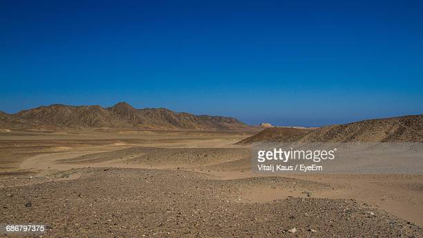 Scenic View Of Landscape And Mountains Against Clear Blue Sky