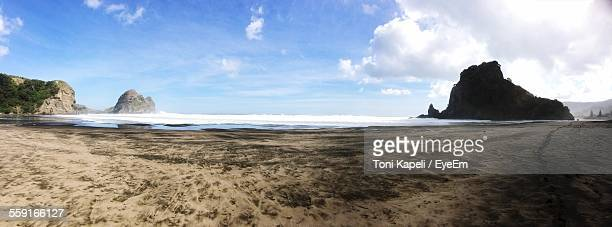Scenic View Of Lion Rock In Piha Beach Against Sky