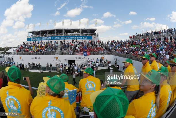 A scenic view of Marc Leishman of Australia and the International Team teeing off at the first tee with the Fanatics in the foreground during the...