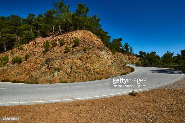 Scenic View Of Mountain Road Against Clear Blue Sky