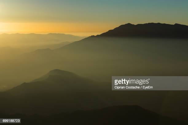 Scenic View Of Mountains In Foggy Weather At Sunset