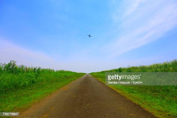Scenic View Of Plane Flying Over Field