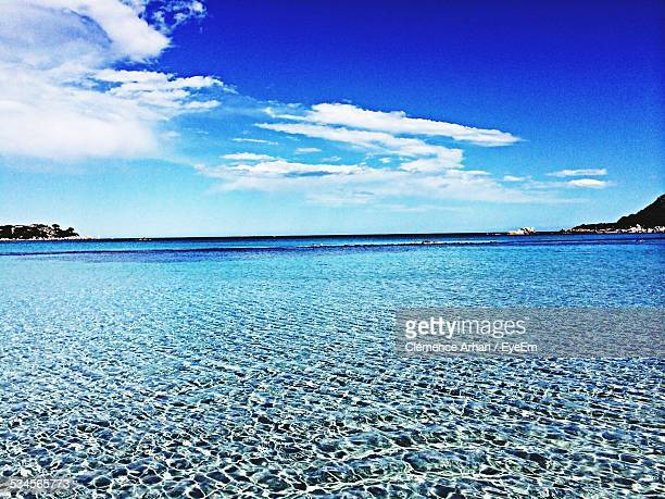 Scenic View Of Rippled Sea Against Blue Sky