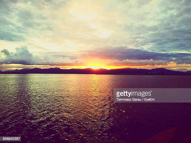 Scenic View Of River Against Cloudy Sky At Sunset