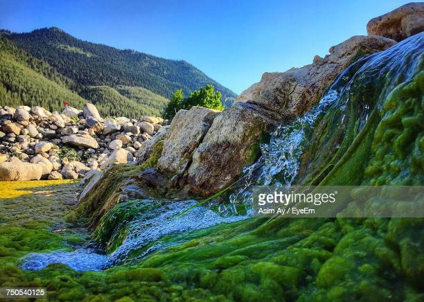 Scenic View Of River Amidst Mountains Against Clear Blue Sky