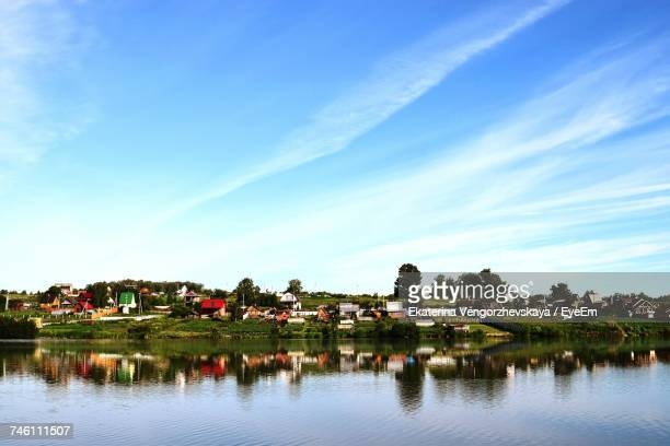 Scenic View Of River By Houses Against Sky