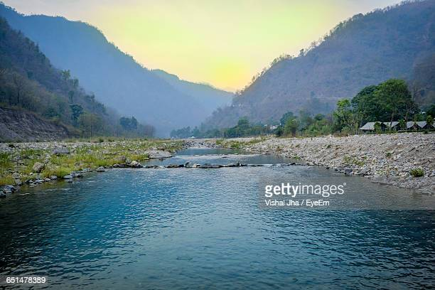 Scenic View Of River By Mountain During Sunrise