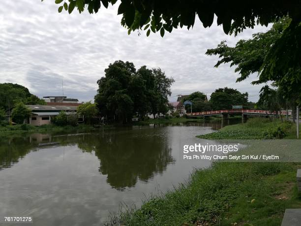 Scenic View Of River By Town Against Sky