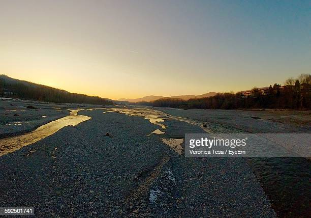 Scenic View Of River Stream Against Sunset Sky