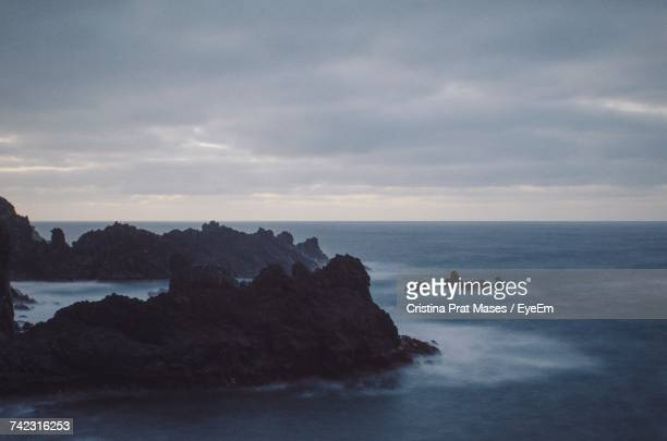 Scenic View Of Rock Formation And Sea Against Sky
