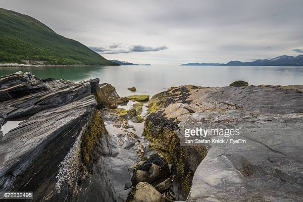 Scenic View Of Rocks And Sea Against Cloudy Sky