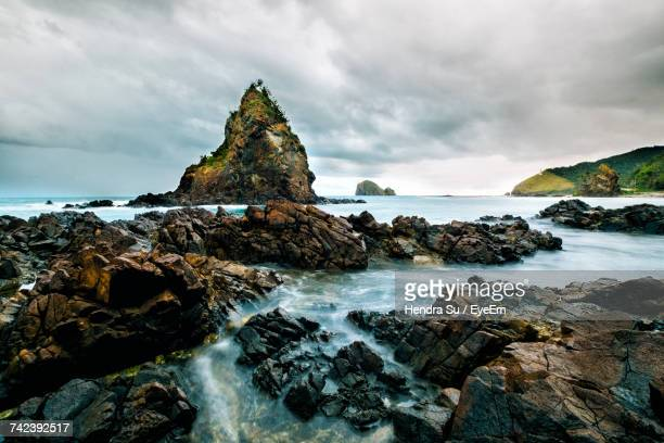 Scenic View Of Rocks In Sea Against Sky