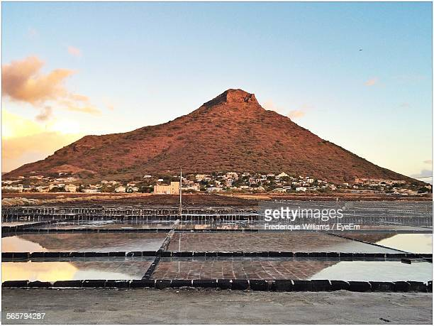 Scenic View Of Salt Field Opposite Mountain Against Cloudy Sky