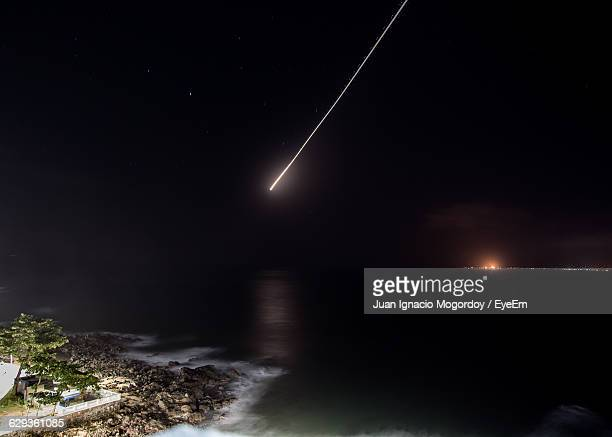 Scenic View Of Sea Against Sky With Comet At Night