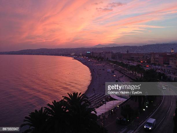 Scenic View Of Sea And City Against Sky During Sunset