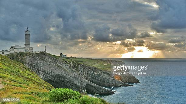 Scenic View Of Sea And Shore Against Cloudy Sky During Sunset