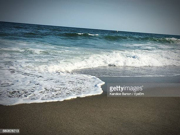 Scenic View Of Sea By Beach Against Clear Sky