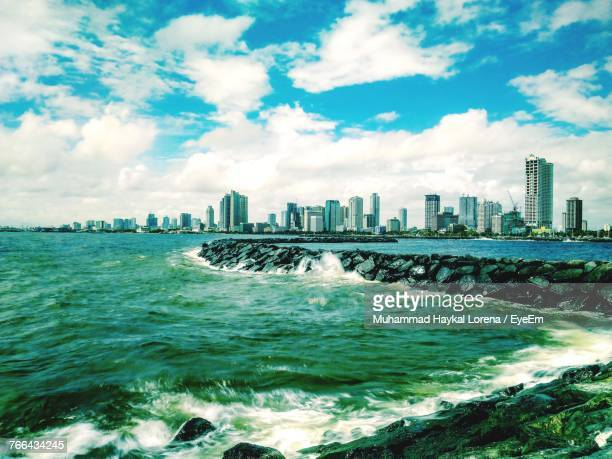 Scenic View Of Sea By City Against Sky