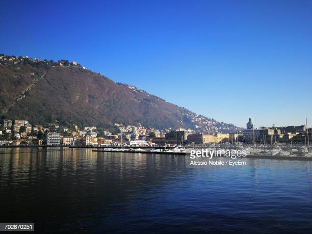 Scenic View Of Sea By Cityscape Against Clear Blue Sky