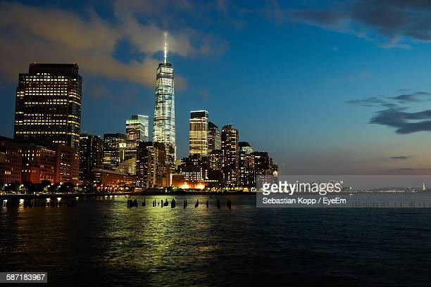 Scenic View Of Sea By Illuminated Cityscape Against Sky At Dusk