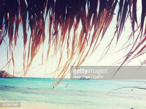 Scenic view of sea through thatched roof