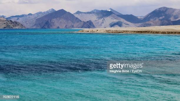 Scenic View Of Sea With Mountains In Background