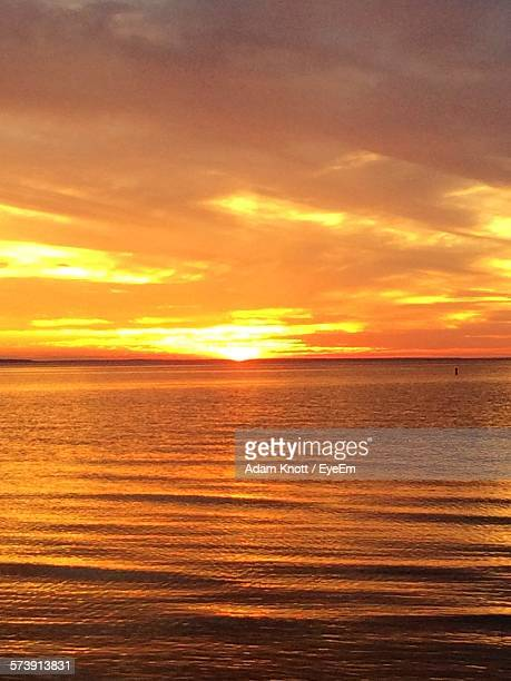 Scenic View Of Seascape Against Orange Cloudy Sky