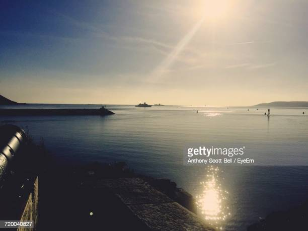 Scenic View Of Seascape Against Sky On Sunny Day