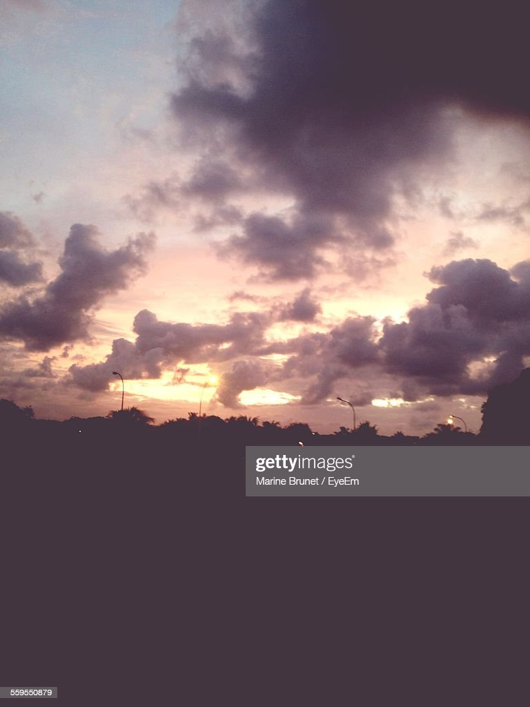 Scenic View Of Silhouette Field Against Cloudy Sky At Sunset