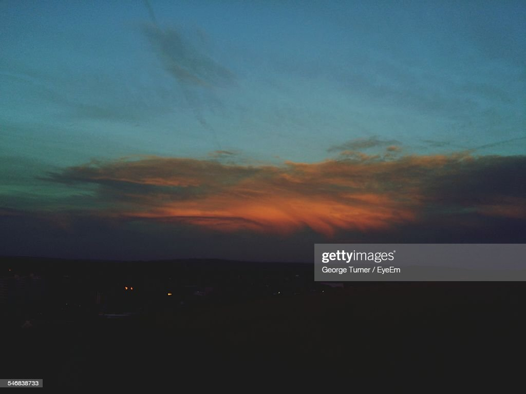 Scenic View Of Silhouette Landscape Against Cloudy Sky At Dusk