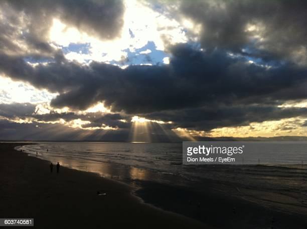 Scenic View Of Silhouette People At Beach Against Cloudy Sky