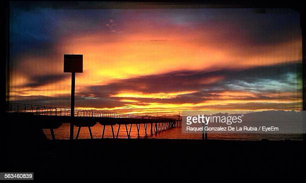 Scenic View Of Silhouette Pier On Sea Against Cloudy Sky During Sunset