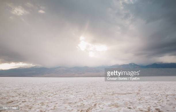 Scenic View Of Snow Covered Arid Landscape Against Cloudy Sky At Death Valley National Park