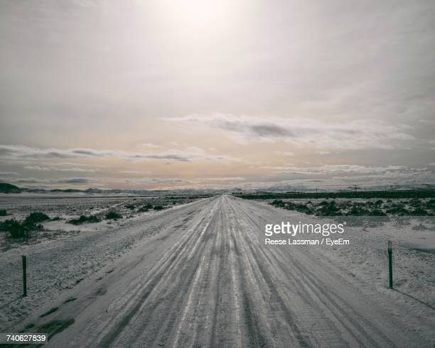 Scenic View Of Snow Covered Road Against Sky During Sunset