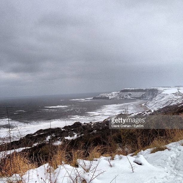 Scenic View Of Snow Covered Shore By Sea Against Cloudy Sky