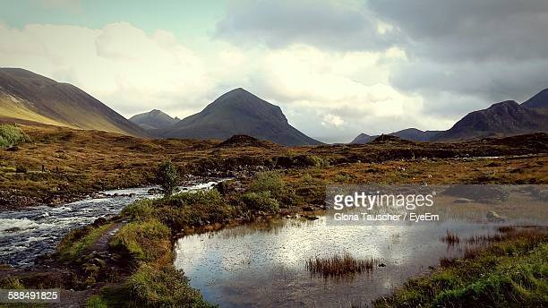 Scenic View Of Stream On Landscape By Mountains Against Cloudy Sky
