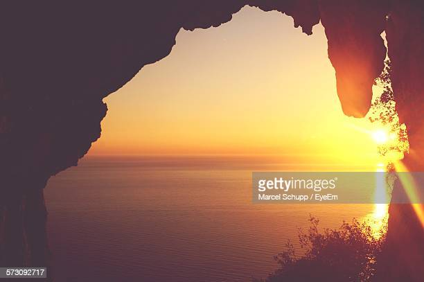Scenic View Of Sunset At Shore Seen Through Cave