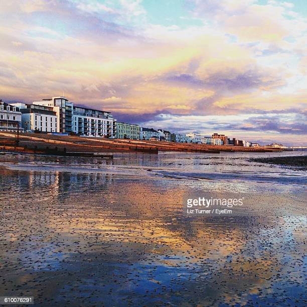 Scenic View Of Wet Beach And Buildings Against Cloudy Sky During Sunset