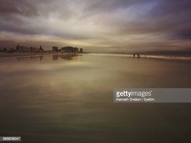 Scenic View Of Wet Beach And Sea Against Cloudy Sky